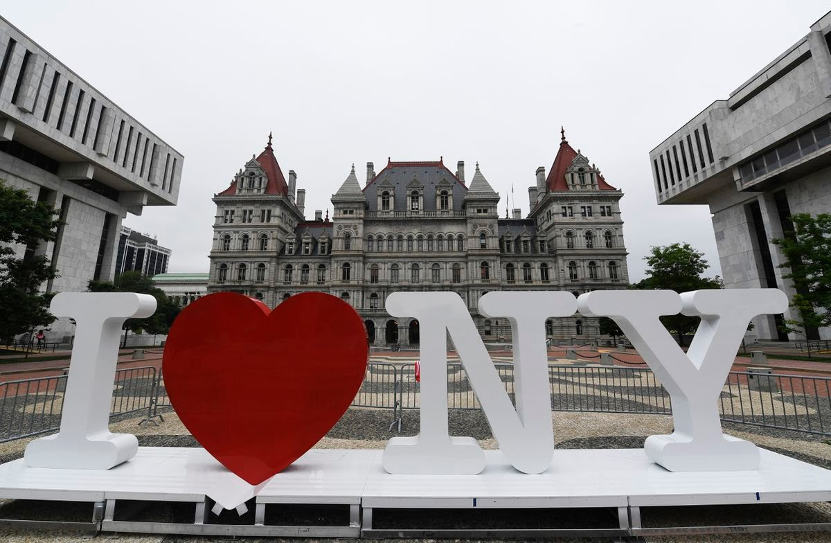 """A new promotional """"I Love NY"""" sign sits in the Empire State Plaza for installation in front of the New York state Capitol in Albany, N.Y. Milton Glaser, the designer who created the """"I (HEART) NY"""" logo and the famous Bob Dylan poster with psychedelic hair, died Friday, June 26, 2020, his 91st birthday."""
